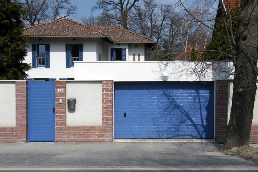 Egyedi kék festésű garázskapu, azonos megjelenésű személybejáró kapuval